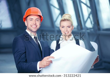 Handsome foreman is beautiful architect are discussing sketches of construction. They are holding a blueprint and looking forward with joy. The man and woman are standing and smiling - stock photo