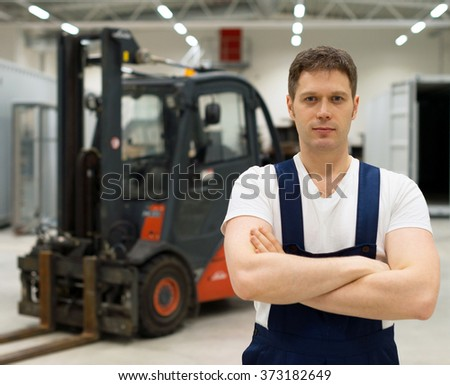 Handsome forklift operator in the warehouse. - stock photo