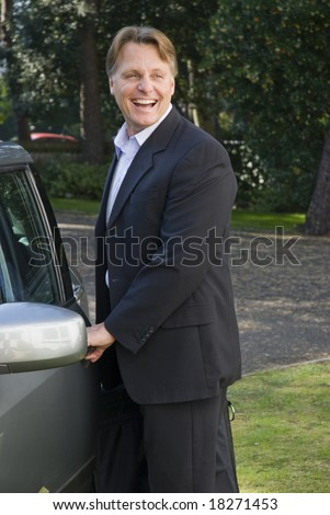 Handsome forties businessman is opening his car door and on his way to work