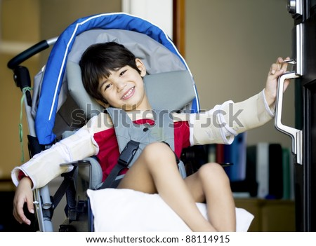 Handsome four year old disabled boy in wheelchair opening front door, smiling a welcome - stock photo