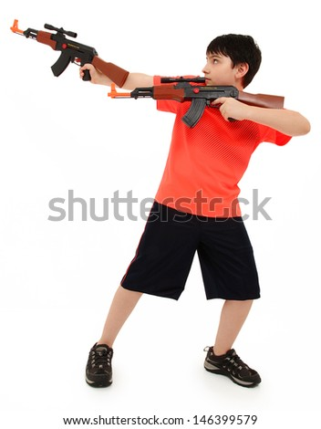 Handsome French American Boy Aiming Two  Plastic Toy AK47 To Side - stock photo