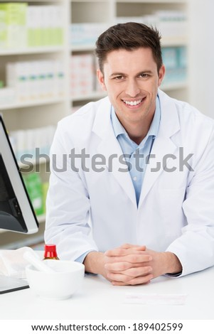 Handsome friendly young pharmacist leaning on the counter in the pharmacy with shelves of stock behind smiling at the camera - stock photo