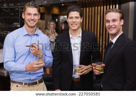 Handsome friends having a drink together at the bar - stock photo