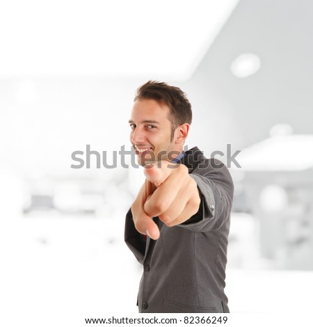 Handsome funny businessman pointing at you