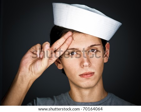 handsome  gallant  young man in the sailor  cap is saluting - stock photo