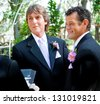 Handsome gay couple getting married in outdoor ceremony. - stock photo