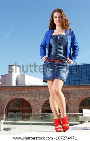 handsome girl wearing short skirt and red high heels standing outside in urban landskape - stock photo