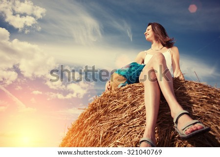 Handsome girl with backpack sitting on haystack outdoors (intentional sun glare and lens flares)