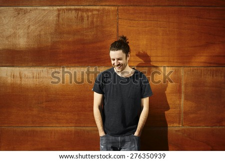Handsome good-looking hipster on city wall smiling happy after walking vacation looking in corner. Male model enjoying sunny holidays under the sun. Young Caucasian man in his twenties.  - stock photo