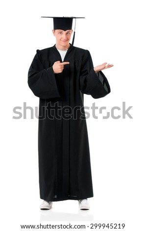 Handsome graduate guy student in mantle showing something, isolated on white background