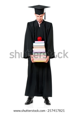 Handsome graduate guy student in mantle with books and apple, isolated on white background - stock photo