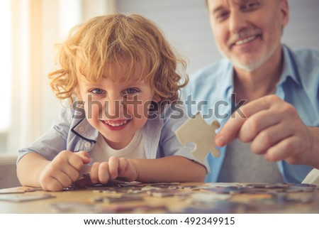 Handsome grandpa and grandson are doing puzzle, looking at camera and smiling while spending time together at home
