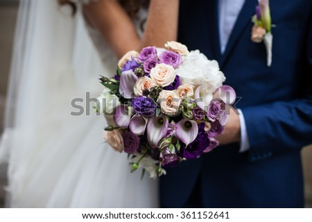 Handsome groom and beautiful bride in white dress holding a bouquet closeup