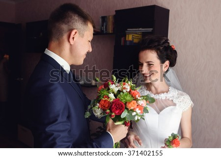 Handsome groom and beautiful bride posing with flowers in hotel room