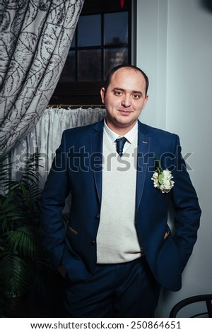 Handsome groom at wedding tuxedo smiling and waiting for bride. Happy smiling groom newlywed. Rich groom at wedding day. Elegant groom in tuxedo costume. Handsome caucasian man in tuxedo. - stock photo