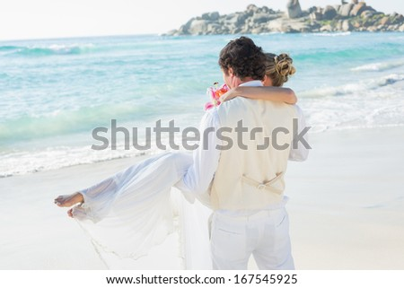 Handsome groom carrying his beautiful wife out to the water at the beach - stock photo