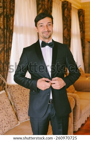Handsome groom getting dressed in his wedding day