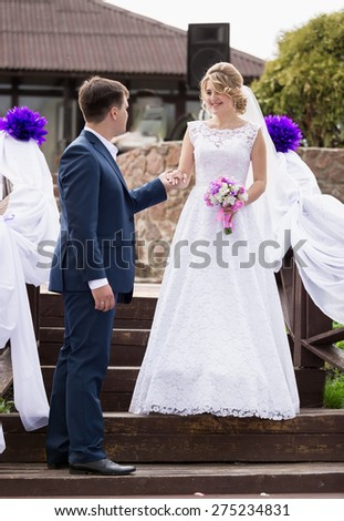 Handsome groom giving hand to smiling bride walking down the stairs - stock photo