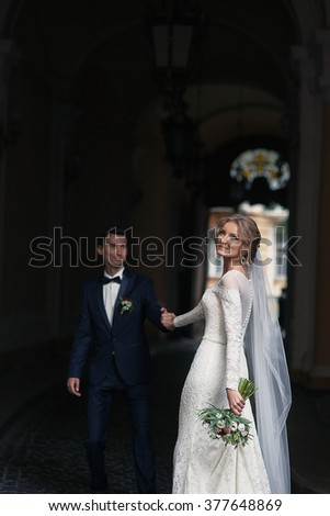 Handsome groom holding hands happy bride in french street - stock photo