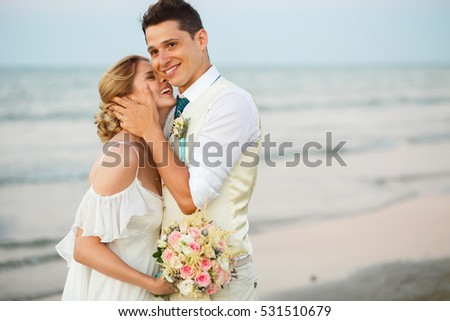 Handsome groom holds bride's face while they stand on sea shore