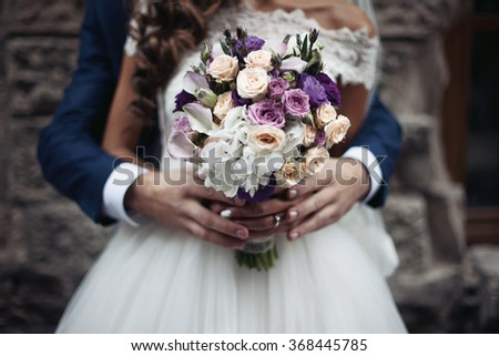 Handsome groom hugging beautiful bride in white dress from behind bouquet closeup - stock photo