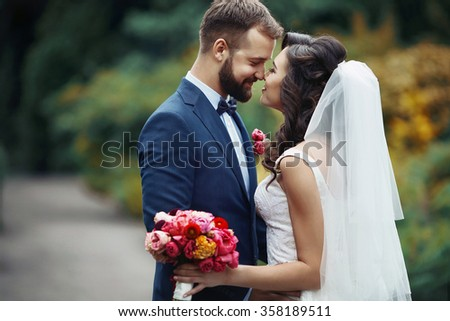 Handsome groom hugging beautiful bride with bouquet in romantic european park - stock photo