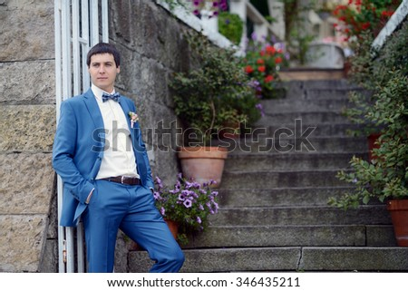Handsome groom in suit on the nature. Male portrait in the park. Beautiful model boy in colorful wedding clothes. Man is posing. Handsome guy outdoors