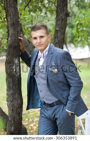 handsome groom in the gray wedding suit in the garden - stock photo