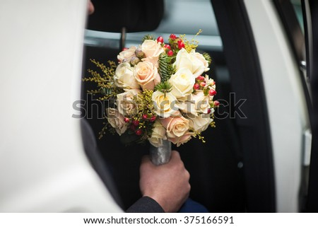 Handsome groom posing with bouquet in wedding car - stock photo