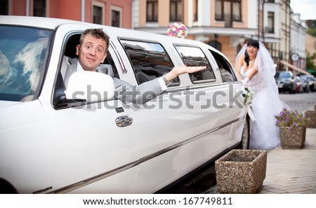 Handsome groom sitting in car while bride pushing it - stock photo