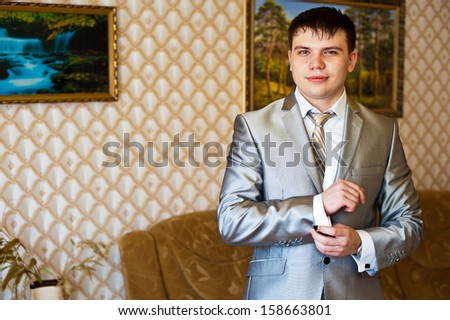 Handsome groom thinking and putting on his bowtie while getting dressed for his wedding. Hands of wedding groom getting ready in suit.  man in a tux fixing his cuff link. - stock photo