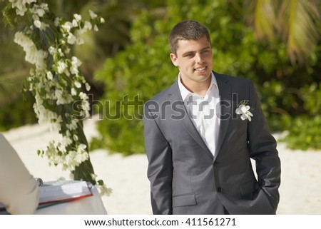 Handsome groom waiting for bride during ceremony on the beach. With beautiful black suit and flower on it. Under flowered arch.