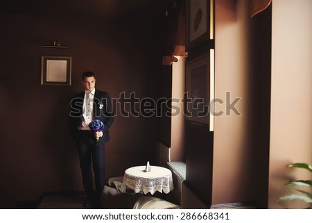 Handsome groom with bouquet of flower in dark room