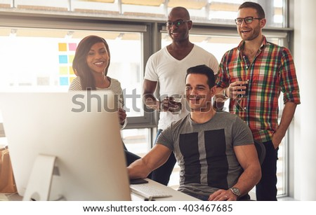 Handsome group of Black, Hispanic and Caucasian young adults at desk smiling while looking at computer monitor in office - stock photo