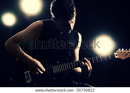 handsome guitarist playing on the stage
