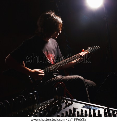 handsome guitarist recording and playing guitar
