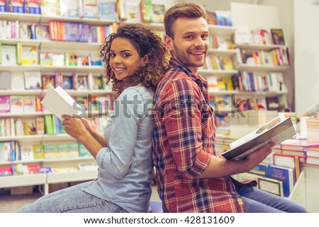 Handsome guy and beautiful girl are reading books, looking at camera and smiling while sitting back to back in the book shop - stock photo