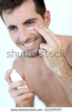 Handsome guy applying concealer around his eyes - stock photo
