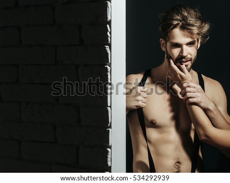 Handsome guy fashion sexy young bearded macho man model with suspenders on pants with female hand on bare muscular torso holds on brick wall and grey background, copy space