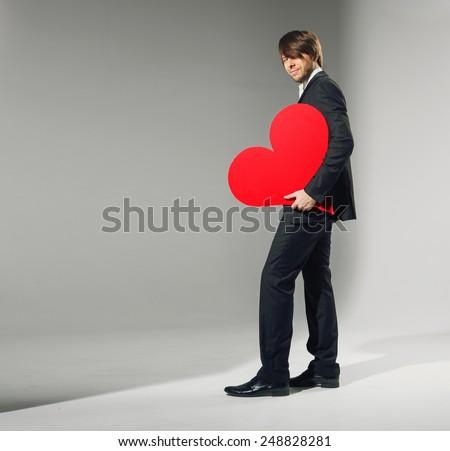 Handsome guy holding heart symbol - stock photo