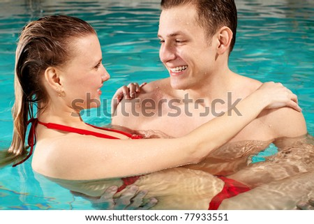 Handsome guy holding his girlfriend and looking at her in swimming pool - stock photo