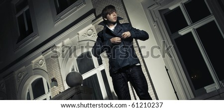 Handsome guy in front of a luxury house - stock photo