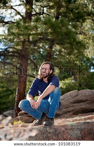 Handsome guy in his 20's in pine forest, nature - stock photo