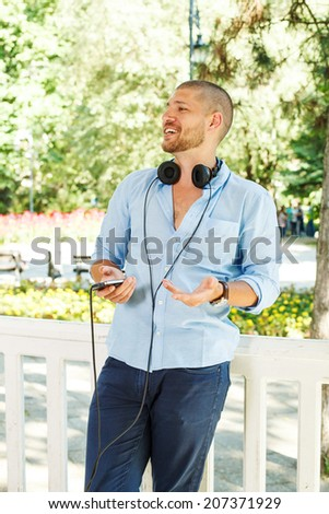 handsome guy in the light blue shirt posing with headphones and a phone in his hand - stock photo