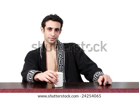 Handsome guy in the morning who just woke up sitting at a table in his robe with a cup, isolated on white