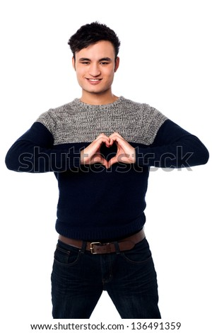 Handsome guy making heart sign with his hands. - stock photo
