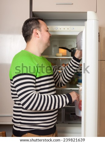 Handsome guy  near opened refrigerator in kitchen at home - stock photo