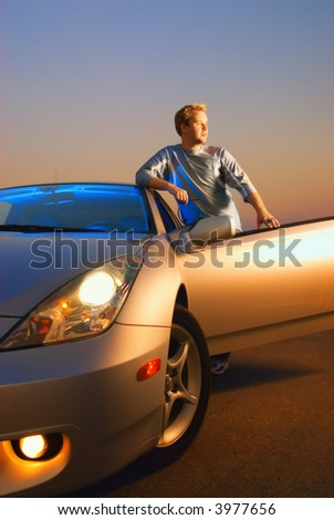 Handsome guy near the modern sport car at sunset time - stock photo