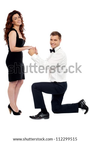 Handsome guy on his knees proposing girl to marry him holding hands of his  beloved - stock photo