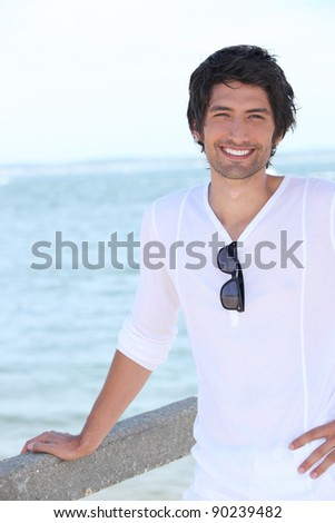handsome guy posing against sea background - stock photo